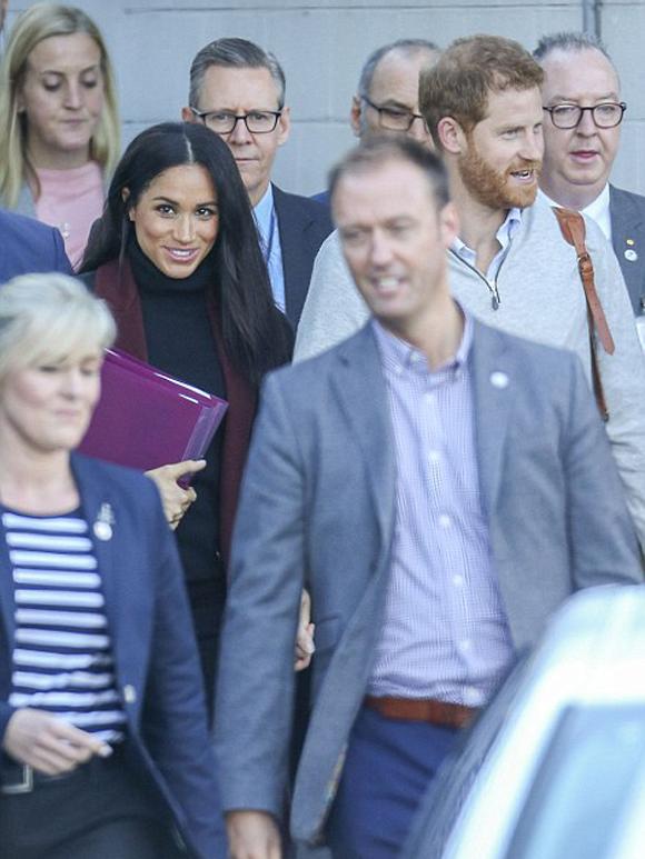 Hoàng tử Harry siết chặt tay vợ, đi giữa đoàn hộ tống khi ra khỏi sân bay Sydney sáng nay, 15/10. Ảnh: Media-mode.