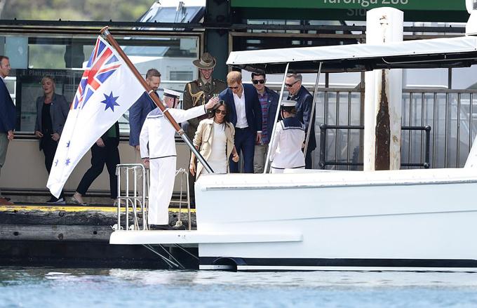 Cặp vợ chồng hoàng gia Anh được hộ tống đi bằng thuyền. Để tiện di chuyển, bà bầu Meghan thay một đôi giày đế bệt màu xanh navy.
