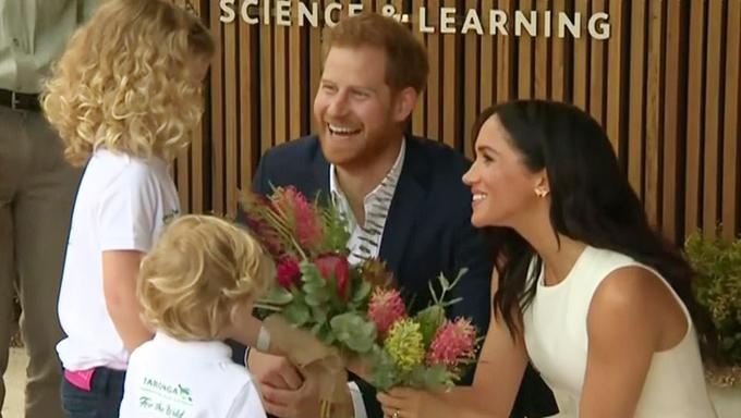 Chào đón hai vợ chồngở cửa của Viện Khoa học và nghiên cứu nằm trong khu vực vườn thú Taronga là hai em bé với bó hoa trên tay.  Để cảm ơn,  Harry - Meghan ngồi hẳn xuống nhận hoa và trò chuyện với chúng.