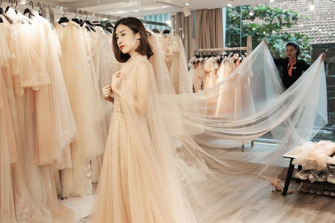 Mỹ Linh thử một mẫu váy cưới dáng chữ A màu kem và kết hợp cùng khăn voan dài theo phong cách châu Âu cổ điển.