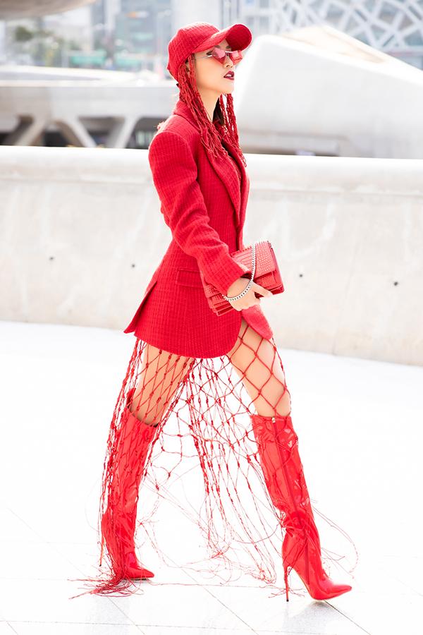 Hoàng Oanh chọnáo vest đỏ áng rộng đi kèm với phần váy lưới để dễ dàng khoe được đôi bốt da bóng. Bên cạnh đó, mẫuclutch của nhà mốt Yves Saint Laurent và mắt kính trendy tạo điểm nhấn cho tổng thể.