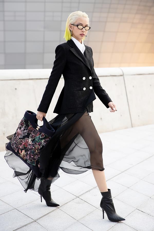 Người đẹp gây bất ngờ khi kết hợp trang phục vest lịch lãm cùng váy lưới quyến rũ đến từ thương hiệu Chanel đình đám. Sử dụng tông đen khá đơn giản cho set đồ lần này, nhưng người mẫu tạo điểm nhấn bằng phụ kiện mắt kính độc đáo, túi xách Chanel thêu hoa nổi bật và bốt mũi nhọn cá tính.