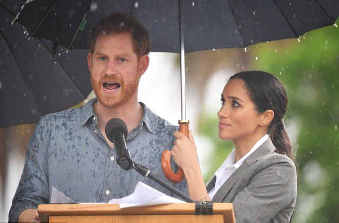 Meghan thay vệ sĩ cầm ô che mưa cho chồng trong buổi phát biểu sáng 17/10 ở Dubbo, bang New South Wales. Ảnh: REX.