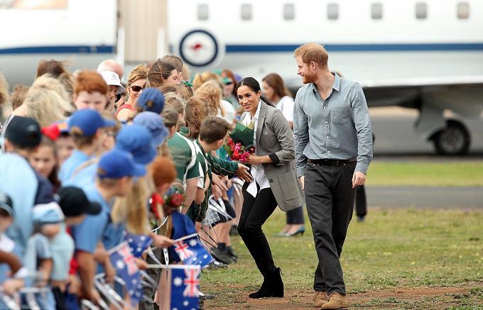 Vợ chồng Meghan được trẻ em chào đón khi hạ cánh xuống sân bay tại Dubbo, bang New South Wales sáng 17/10. Ảnh: REX.
