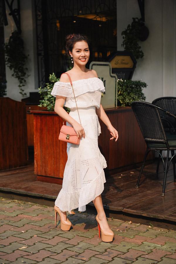 Mẫu váy trắng trễ vai được ca sĩ gốc Quảng Ninh mix cùng túi hiệu ton hồng cam có giá khoảng 1.000 USD.