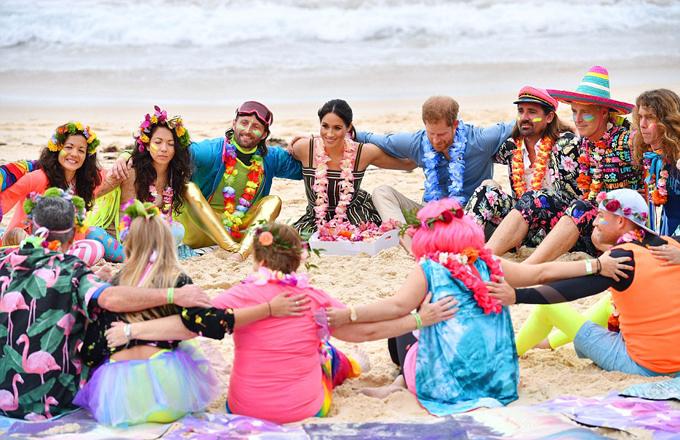 Vợ chồng Harry - Meghan cùng các thành viên OneWay tạo thành vòng tròn chống cảm xúc tiêu cực trên bãi biển Bondi Beach, Sydney, sáng 19/10. Ảnh: PA.