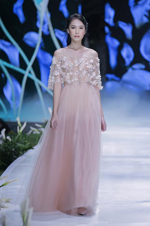 NTK Phương Linh tập trung khai thác tối đa nét yêu kiều, duyên dáng của các nàng dâu trong bộ sưu tập thời trang mới. Điểm nhấn của trang phục là những cánh hoa 3D được đính kết một cách nghệ thuật. Thiết kế trễ vai khoe khéo bờ vai trần thon thả của cô dâu mới.