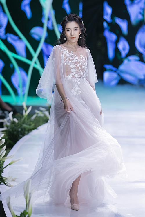 Váy cưới chữ A được nhấn nhá bởi những cánh hoa thêu nổi tỉ mỉ trên nền voan mỏng xuyên thấu.