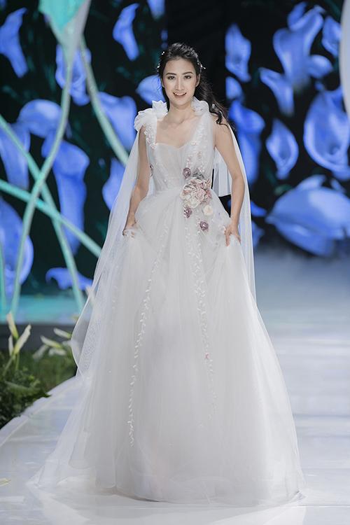 Váy cưới xòe nhẹ được điểm thêm cụm hoa ngang eo mang vẻ nữ tính và bay bổng, khiến nàng dâu dễ dàng đem lòng mê mẩn. Tà phụ được đính trên cầu vai giúp từng cái nhấc tay, bước đi của cô dâu trở nên nhẹ nhàng, mềm mại hơn.