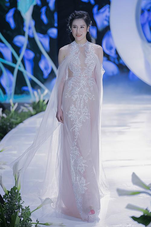 Hoa văn thêu ren sắc sảo trên nền vải voan mờ tạo nét kiêu sa, đầy nữ tính cho cô dâu mới. NTK chọn hot trend cổ hai trong một để chiếc váy thêm gợi cảm, tinh tế.