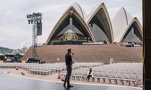 Meghan một mình ngồi ở hàng ghế khán giả xem chồng diễn tập phát biểu