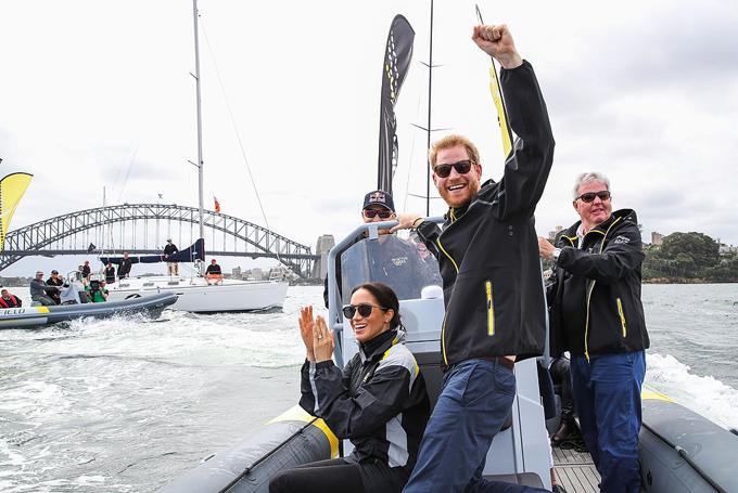 Vợ chồng Harry - Meghan xem giải đua thuyền trên sông Sydney chiều 21/10. Ảnh: Reuters.