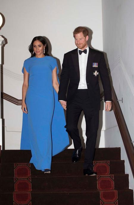 Meghan nắm chặt tay chồng khi đến bữa tiệc chiêu đãi của tổng thống Fiji. Ảnh: AP.