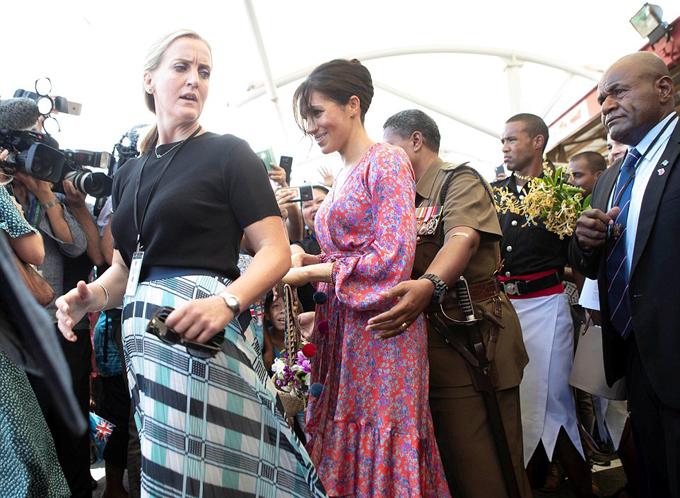 Meghan được nữ vệ sĩ riêng (mặc áo đen) và sĩ quan địa phương hộ tống ra khỏi chợ Suva, Fiji sáng 24/10. Ảnh: Reuters.