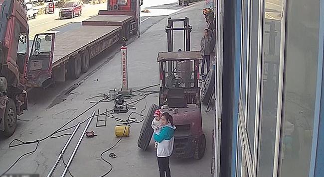 Bà mẹ bế con trai chưa đầy 1 tuổi đứng cạnh chiếc lốp ôtô đang được bơm hơi ở một garage tại thành phố Đan Giang Khẩu, tỉnh Hồ Bắc, Trung Quốc hôm 12/10. Ảnh: Asiawire.