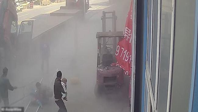 Nhân viên garage tại Đan Giang Khẩu, tỉnh Hồ Bắc, Trung Quốc đỡ bà mẹ và đứa bé dậy sau vụ tai nạn nổ lốp ôtô hôm 12/10. Ảnh: Asiawire.