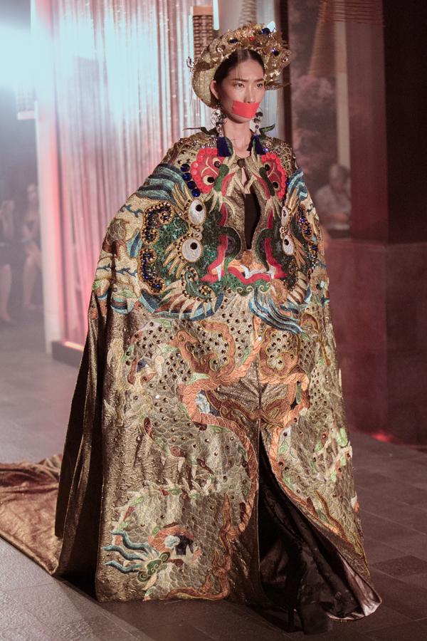 Người mẫu Trang Phạm hoá thân thành hoàng hậu đầy uy nghi, miệng được băng kín khi catwalk.