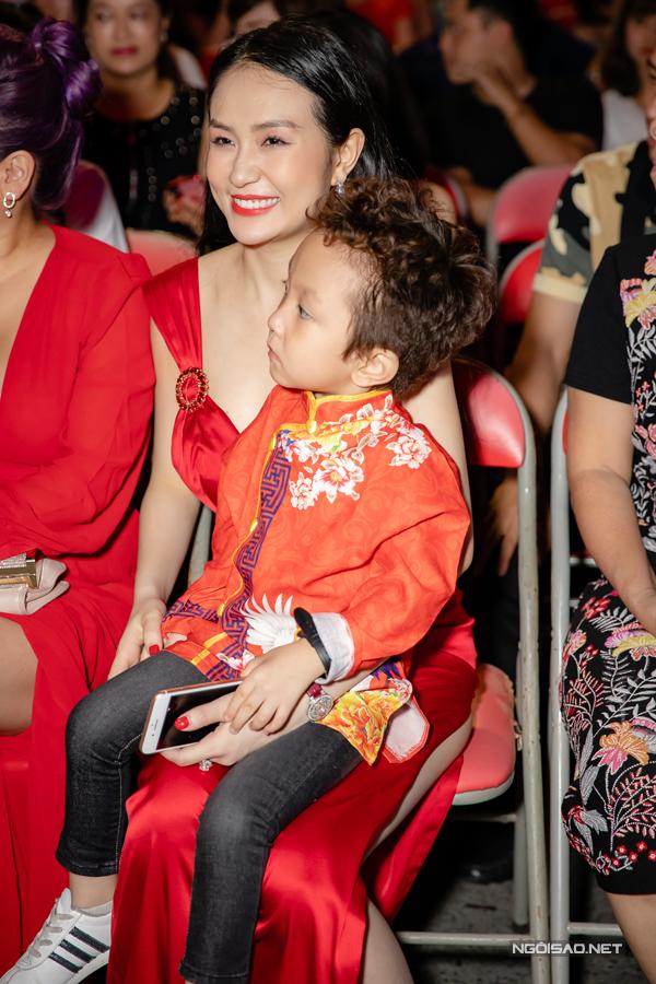 Su Hào mặc áo dài đỏ thêu hoạ tiết mix quần jeans. Cậu bé ngoan ngoãn ngồi trong lòng mẹ, chờ đến giờ xem bố biểu diễn.