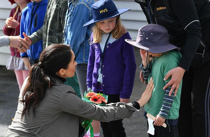 Meghan chạm vào cậu bé 5 tuổi Joe Young để giúp em bình tĩnh, nín khóc ở bên ngoài quán cà phê Maranui, Wellington, New Zealand sáng 19/10. Ảnh: AP.