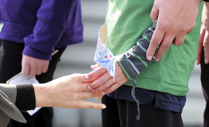 Cái chạm tay thân thiện giữa Meghan và fan nhí 5 tuổi ở trước cửa quán cà phê Maranui, Wellington, New Zealand sáng 19/10. Ảnh: AP.