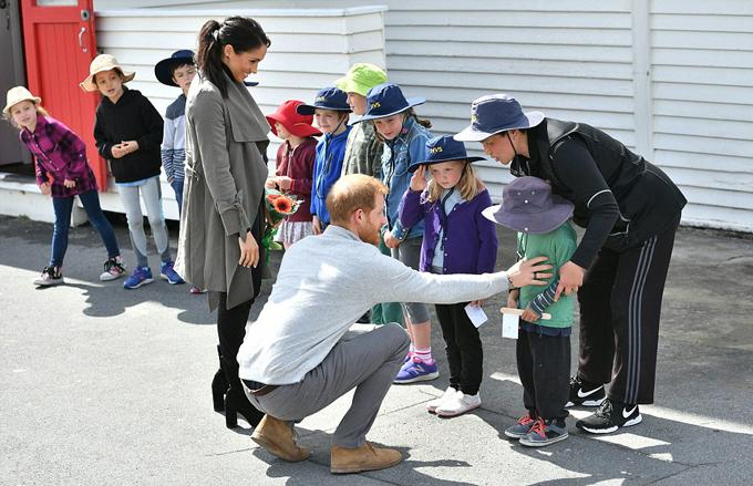 Hoàng tử Harry trò chuyện, chọc cười với cậu bé Joe Young (5 tuổi) bên ngoài quán cà phê Maranui, Wellington, New Zealand sáng 19/10. Ảnh: AP.