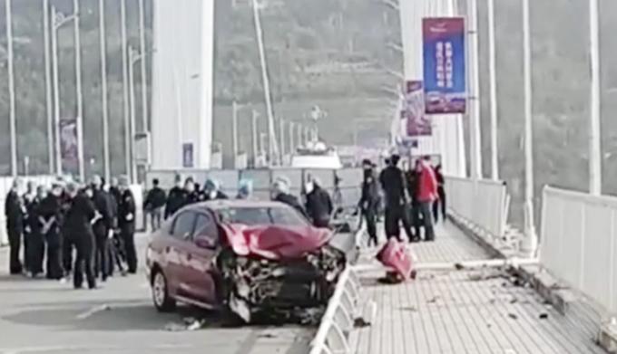 Chiếc xe hơi màu đỏ bị nát đầu sau vụ va chạm với xe buýt trên cầu bắc qua sông Dương Tử sáng 28/10. Ảnh: Sina.