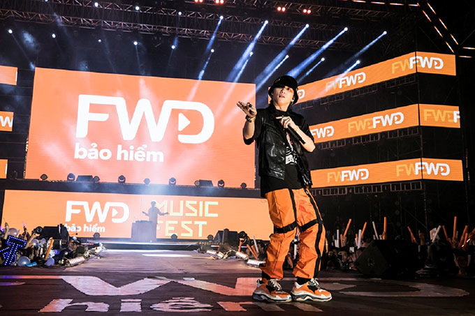 Ca sĩ diện trang phục trẻ trung với áo thun, quần cam sặc sỡ và giày sneaker hầm hố..