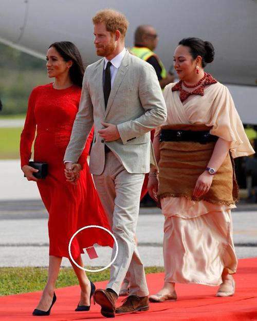 Nữ công tước xứ Sussex để lộ tem mác của chiếc váy Self Portrait 444 USD khi xuống máy bay ở Tonga chiều 25/10. Ảnh: Reuters.