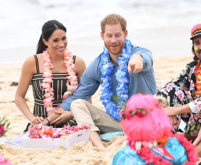 Vợ chồng Meghan ngồi trên cát ở bãi biển Bondi, Sydney hôm 19/10. Ảnh: PA.