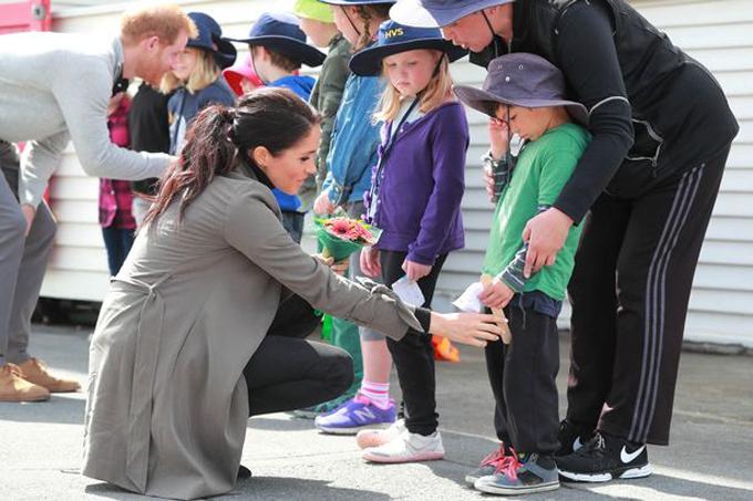Nữ công tước xứ Sussex vỗ về cậu bé 5 tuổi Joe Young bên ngoài quán cà phê Wellington, New Zealand hôm 29/10. Ảnh: PA.