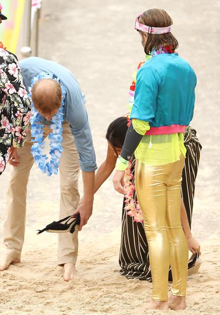 Harry giúp vợ cất giày để đi lại trên cát thoải mái hơn.