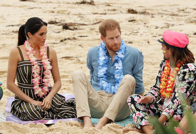 Harry và Meghan thoải mái cởi giày dép, ngồi xuống cùng người dân để trò chuyện.