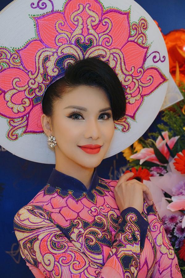 Người đẹp 32 tuổi diện áo dài họa tiết hoa sen của nhà thiết kế Minh Châu dự thi trang phục dân tộc. Cô tự tin với vẻ duyên dáng, rạng rỡ không thua kém bạn bè quốc tế.