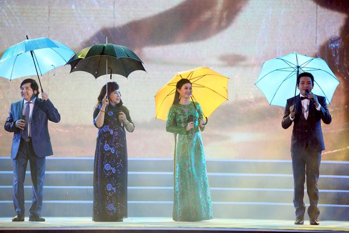 Từ trái qua: các nghệ sĩ Chí Tâm, Lệ Thủy, Quế Trân và Trọng Phúc kết hợp hát ca cổ Hà Tiên - Khúc hát tự hào. Trời bất ngờ đổ mưa nhưng các nghệ sĩ vẫn nhiệt tình cầm ô biểu diễn.