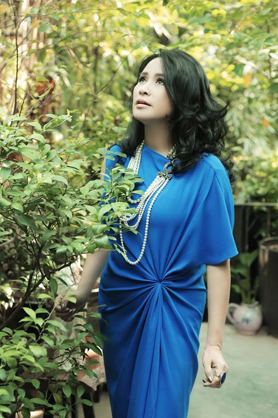 Từ câu trúc của các mẫu váy lụa suông, đầm nhấn eo thường mang lại cảm giác thoái mái và vẫn giúp phái đẹp tôn nét gợi cảm. Thanh Lam chọn vòng cổ ngọc trai để phối hợp cùng váy xanh bắt mắt.