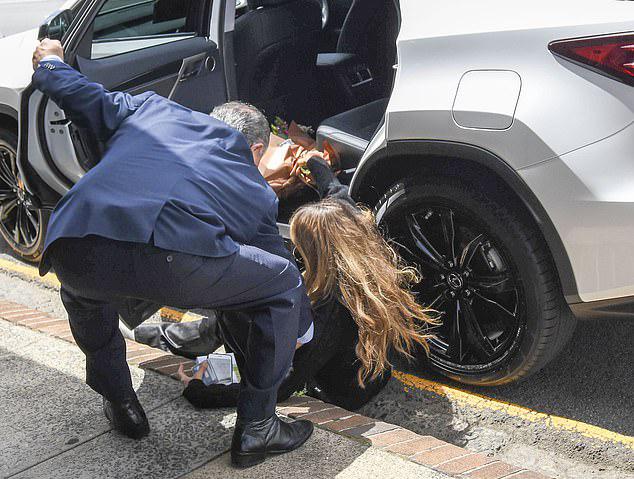 [Caption]Siêu mẫu dường như khá đau sau tai nạn này. Elle Macpherson phải nhờ tài xế đỡ lên xe.