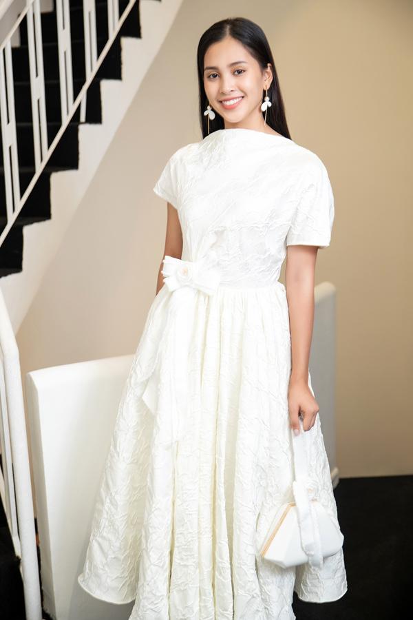 Tiểu Vy xinh xắn khi diện bộ váy họa tiết hoa trà my, phụ kiện bông tai, xúi xách cầm tay ton-sur-ton trắng.