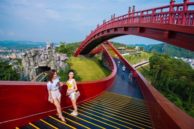 Chiếc cầu Koi đỏ rực uốn lượn tựa dải lụa bồng bềnh giữa mây trời Hạ Long xanh ngắt, selfie hay đặt chế độ chụp panoramo cũng đều cho bạn những bức ảnh xuất sắc.