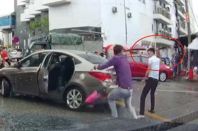 Nam thanh niên cầm dao (vòng tròn đỏ) đuổi chém tài xế ôtô. Ảnh: Cắt từ video.