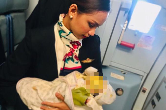 Nữ tiếp viên trẻ bế em bé và nhẹ nhàng cho bé bú để bé ngủ yên, không quấy khóc. ẢnH: Mercury Press & Media.