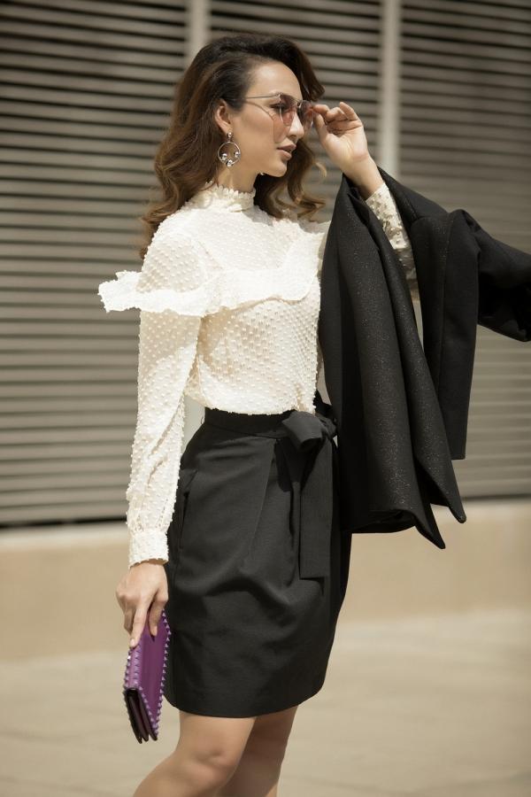 Trung thành gam màu trắng đen, ựa chọn chiếc váy bó màu đen với điểm nhấn là phần nơ ở eo kết hợp với áo thun trắng tay dài phù hợp cho tính chất công việc kinh doanh.
