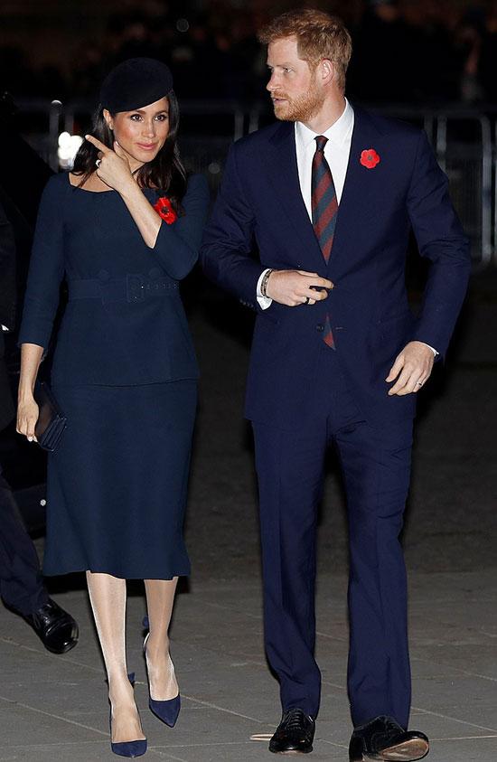 Nữ công tước xứ Sussex thanh lịch trong bộ váy mày xanh navy cổ thuyền với hai hàng cúc trước ngực và thắt lưng to bản ở phần eo, để lộ chiếc bụng bầu đang ngày càng nhô to. Đồng thời, để phù hợp với trang phục, Meghan đi lại đôi giày yêu thích của Aquazzura, trị giá 560 USD.