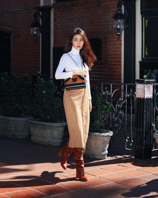 Diễm My sang chảnh với set đồ thu đông khi chọn thêm bốt da cổ cao, túi Louis Vuitton tạo điểm nhấn khi diện áo thun cao cổ, chân váy vải nỉ.