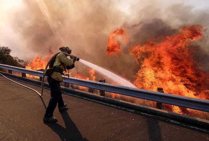 Lính cứu hỏa nỗ lực dập lửa từ trên tuyến đường 118 của California hôm 12/11. Ảnh: AP.
