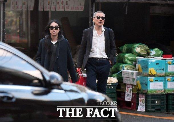The Fact ghi lại hình ảnh diễn viên 36 tuổi Kim Min Hee và đạo diễn Hong Sang Soo (58 tuổi) tay trong tay đi mua sắm tại một cửa hàng rau quả thuộc khu Hanam, Gyeonggi-do hôm 9/11. Trong khi vị đạo diễn 58 tuổi tay xách nách mang lỉnh kỉnh hàng hóa, người yêu ông thảnh thơi dạo bước bên cạnh.