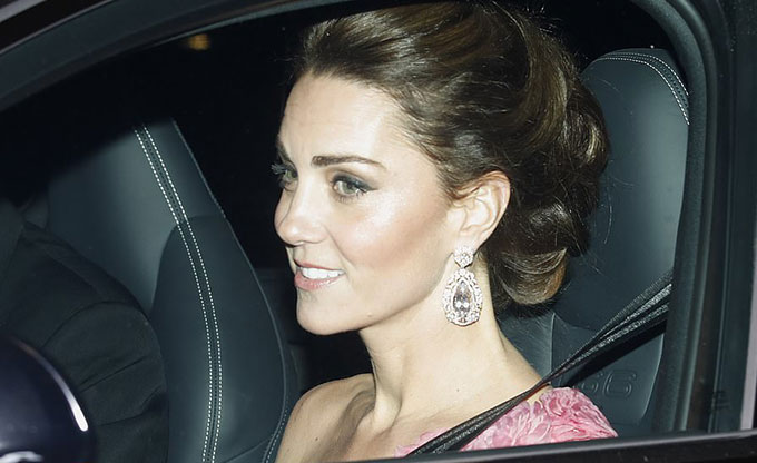 Kate mặc váy hồng lệch vai, tóc búi kiểu cách, đeo bông tai kim cương, được chồng, Hoàng tử William, chở đến Điện Buckingham tối 14/11. Ảnh: AP.