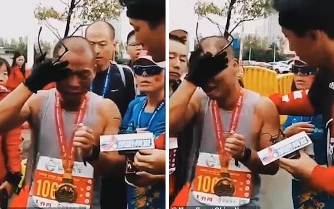 Anh Li Gang bật khóc khi cầm ảnh con trai cán đích của giải chạy 42 km Nanchang International Marathon hôm 11/11 tại thành phố Nam Xương, Trung Quốc. Ảnh: China News.