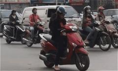 Người phụ nữ đứng giữa đường lướt điện thoại, mặc kệ xe cộ qua lại