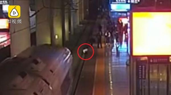 Wang được kéo lên khỏi đường ray ngay trước khi đoàn tàu đi qua. Ảnh: Pear.