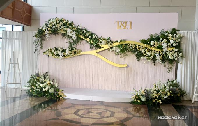 Backdrop đón khách được trang trí hoa tươi đơn giản cùng tên viết tắt của Trương Nam Thành và bà xã Thu Huyền.